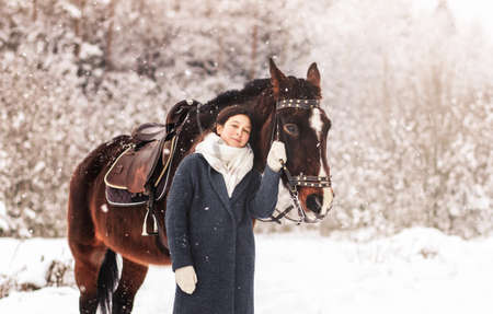 Young beautiful girl on a walk with a horse in winter in the woods