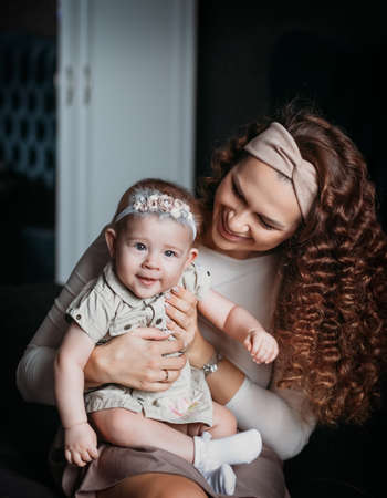 Young beautiful mother holds her baby daughter in her arms and looks at her