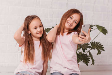 Two girls smile happily and take a selfie photo on a smartphone in a white room
