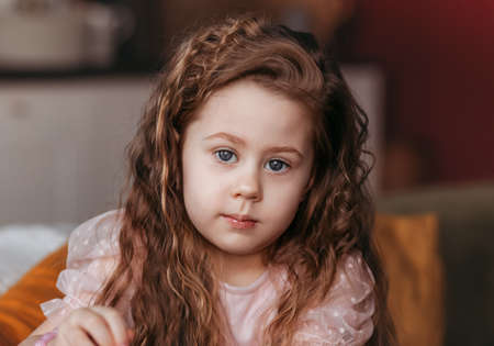 Portrait of a close-up of a little girl with long curly hair