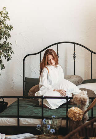 A young beautiful girl with long hair sits on a bed with pillows. Woman enjoying morning awakening. The concept of home coziness and comfort.