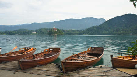 view over Lake Bled, Julian Alps, boats and church on the island, sunny day, Bled, Slovenia