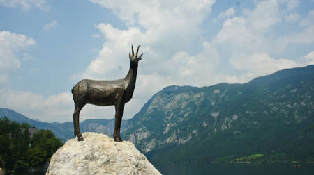 view of the lake Bohinj, monument and Julian Alps mounntains, sunny day, Slovenia