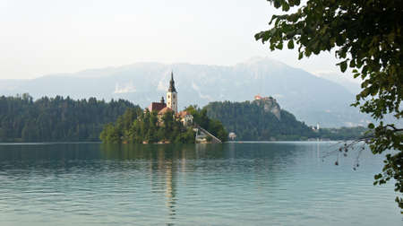 view over Lake Bled, Julian Alps mountains and church on the island, sunny day, Bled, Slovenia