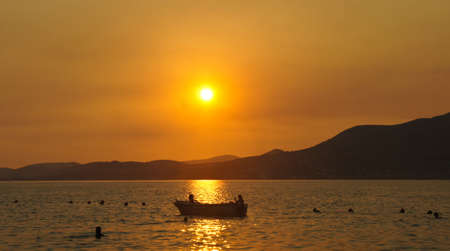 Sunset with a boat on the water on Ciovo island in Croatia near Trogir city