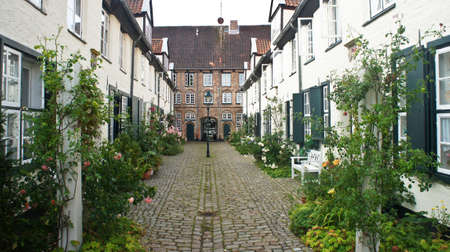 Beautiful cozy courtyard with old houses and flowers in the street of old town, Lubeck