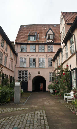 Beautiful courtyard with bench, plants and flowers in the street of old town, Lubeck