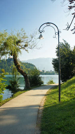 Road around the Bled lake, Julian Alps mountains and Bled Castle, sunny morning, Bled