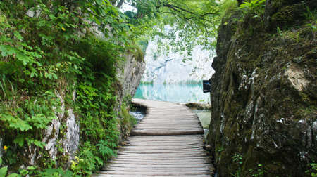 Wooden pathway over the water between rocks, Plitvice Lakes in Croatia Reklamní fotografie