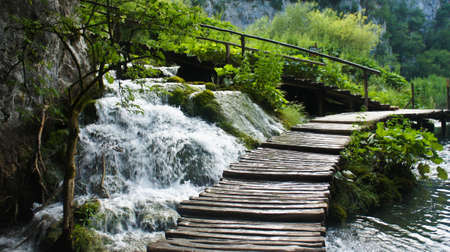 Beautiful cascade waterfalls and wooden pathway over the water, Plitvice Lakes in Croatia Reklamní fotografie