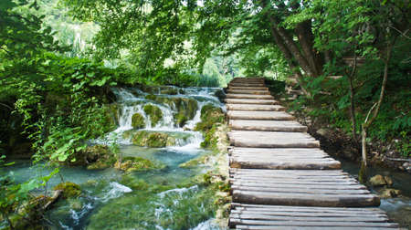 Cascade waterfalls and wooden pathway over the water, Plitvice Lakes in Croatia