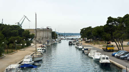 Trogir, Croatia - View of St. Mark s Fortress in old town, channel with boats, sunny day