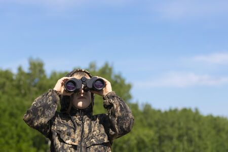Scout boy looks through binoculars on camping trip in green forest