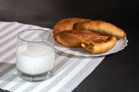hot homemade patties from oven with glass of milk on table. Rustic traditional pastries. Banque d'images