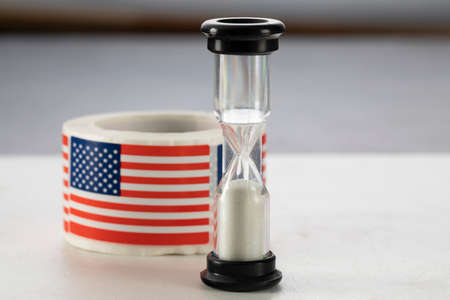 Hourglass with American flag on tape. Independence Day concept.