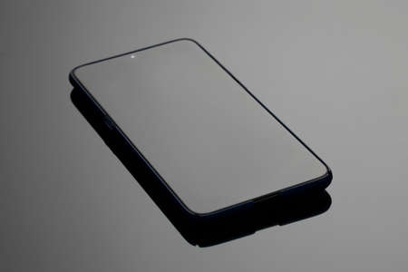 Black large screen smartphone with shadow on glass surface
