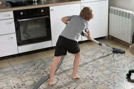 6-year-old boy is cleaning house, vacuuming kitchen floor. helps mom