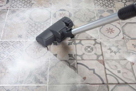 Vacuum cleaner on porcelain stoneware floor with copyspace for text message