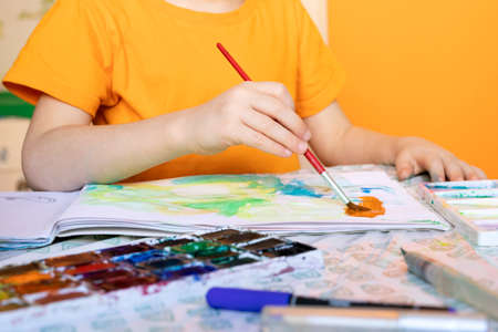 art painting, childrens hands holding brush and drawing of orange paint.