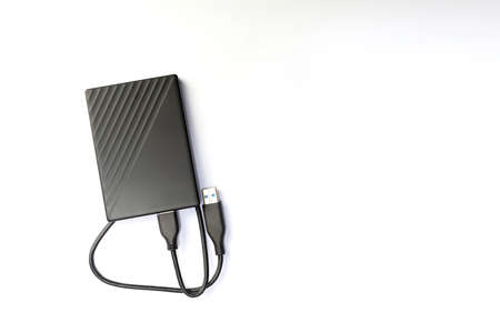 External compact SSD-drive with USB cable for writing, reading and storing data. on white background, top view