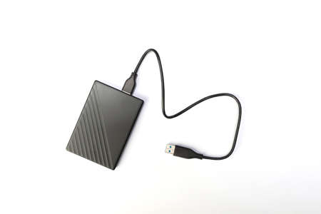 Hard drive or HDD on white background. external hard drive for storing memory with wire. flat lay 免版税图像