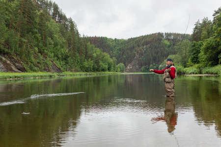 elderly fisherman person using flyfishing rod in mountain river in waterproof cloth