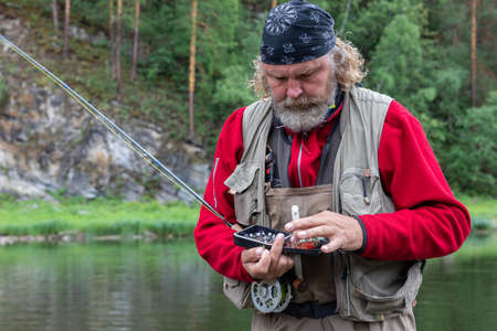 Mature fly fishing fisherman picks up flies for fishing rod equipment. make ready angling