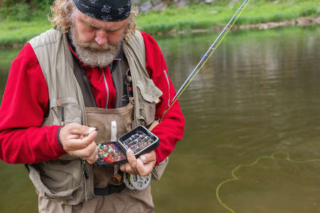 Serious elderly bearded fisherman on river bank holding rod and tackle box selects fly fishing lure would be better. Copy space. Fly-fishing, active leisure, outdoors, recreational fishing
