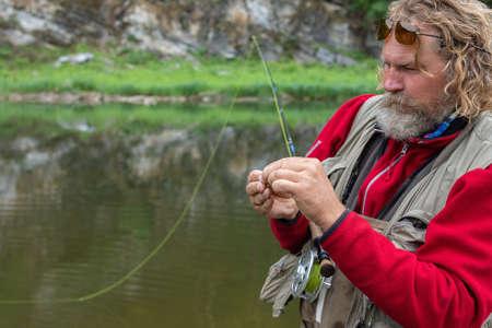 Mature fly fishing fisherman in polarizing glasses tying fly of fishing hook on fishing rod 스톡 콘텐츠