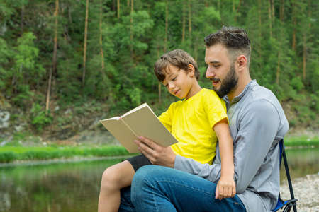 Father and son reading book in park in summer day.