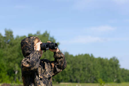 Happy kid playing outdoors with binocular. Travel and adventure concept.