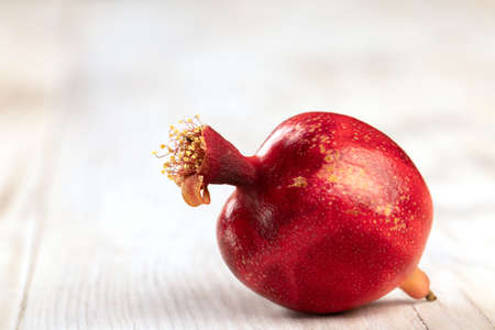Red ripe pomegranate fruit lies on light wooden background