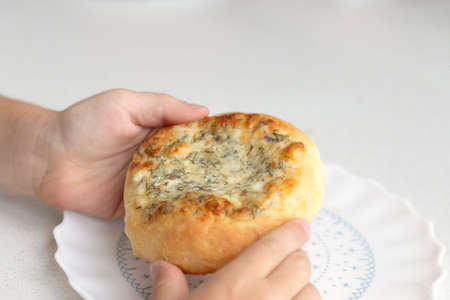 child holds treat in his hands. Patties with cheese and herbs. Russian pastry vatrushka Stok Fotoğraf