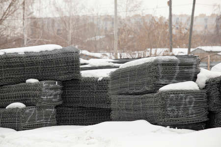 Wire mesh steel for reinforcing. Steel bars stacked for construction, roped with metallic wire and marked with white paint stacked outdoors and covered with snow. Building materials storage on open air