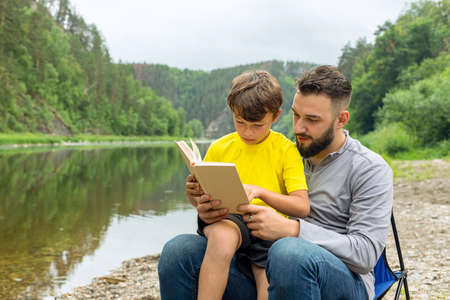 Father and son reading book while sitting outdoor on green natural background.