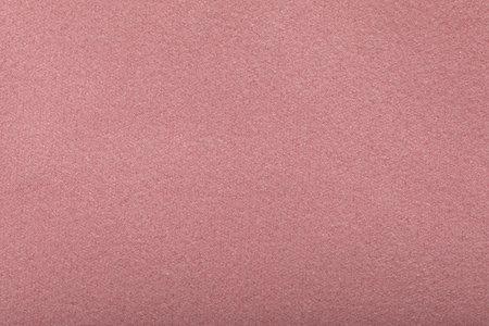Fine grain pink texture background. Velvet scarlet matte background of peach suede fabric.