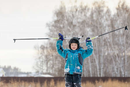 Happy little boy raised his hands in victory when he climbed snowy mountain. Children skiing.
