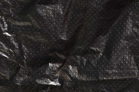 black cellophane bag background texture. plastic surface is wrinkly and tattered making abstract pattern.