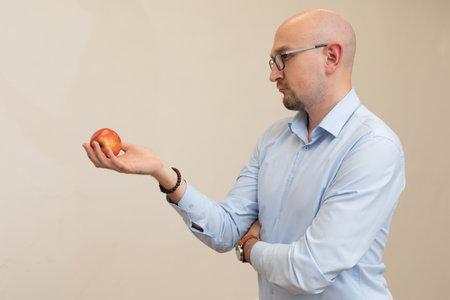 handsome adult bald man holds red apple over light background.