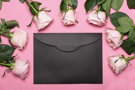 Pink roses on pink backdrop with black blank envelope and copy space. Stock fotó