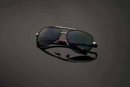 Aviator black sunglasses in round frame on mirror background. Glasses summer collection
