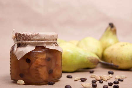 Homemade fruit pear jam in glass jar on table with pears and coffee beans in background