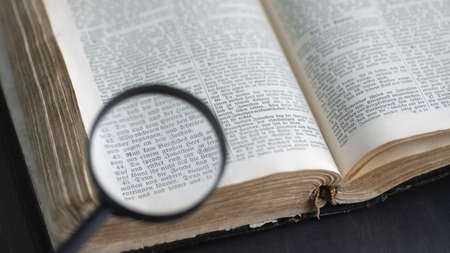 Opening ancient bible, text reading through magnifying glass. Search for truth and meaning of life. Religious book. Russia, 27.12.2020 Stock Photo