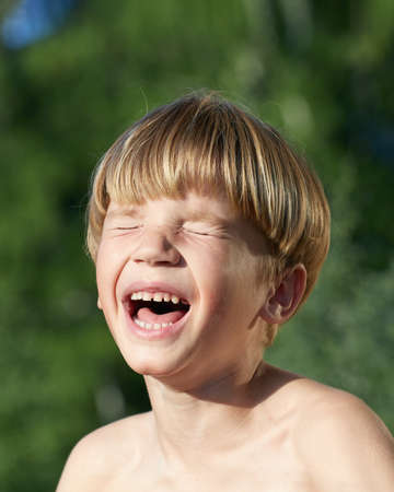 portrait of moody screaming little boy with blonde hair in outdoor