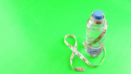 Concept of healthy lifestyle, sports training, weight loss. space for text. Water bottle on green background. Stockfoto - 168139348