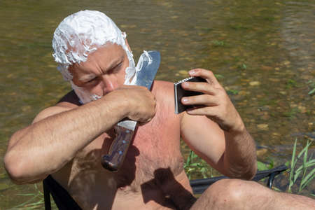 Naked middle-aged man his head and face smeared with shaving foam shaves cheek with huge knife holding blade in hand looking at phone sitting on chair by pond on natural background. Morning on hike.
