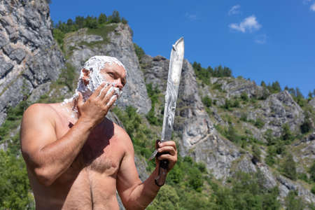bald desperate man shaves his cheek with long knife phone on natural background. Morning on hike. Destination experience lifestyle concept.