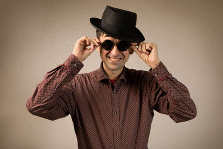 Trendy fashion young caucasian in hat and round sunglasses  smiling touching eyewear looking at camera portrait