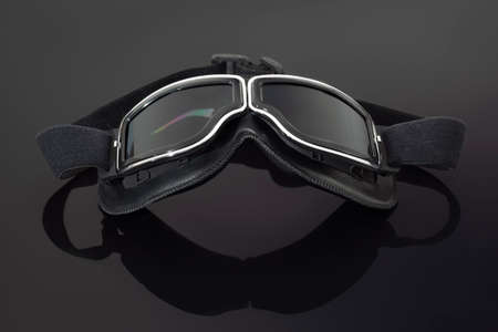 Close-up of black vintage motorcycle race goggles with reflection on mirrored black background. History of motorsport. Collector's item. Eye protection.