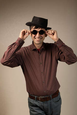 Brutal macho man in hat and round sunglasses standing isolated on studio copy space background. Trendy fashion young caucasian guy smiling touching eyewear looking at camera portrait